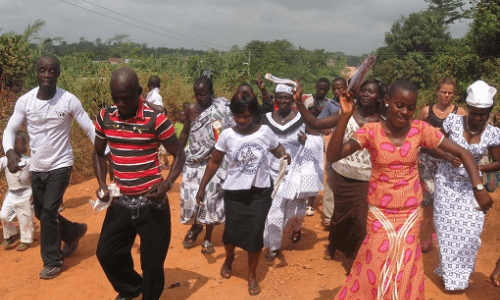 African life, church go-ers dancing on their way to church